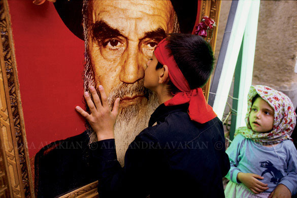 A boy kisses a portrait of the late Ayatollah Khomeini