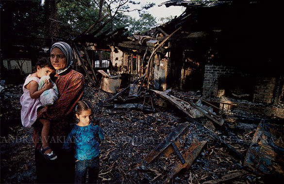 A woman stands outside the ruins of a burned mosque with her two children