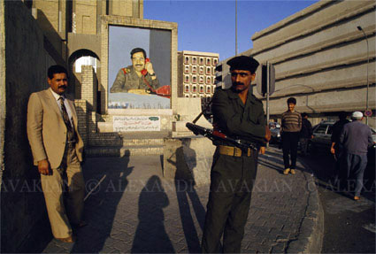 An Iraqi minder standing on the street, with a portrait of Saddam Hussein behind him
