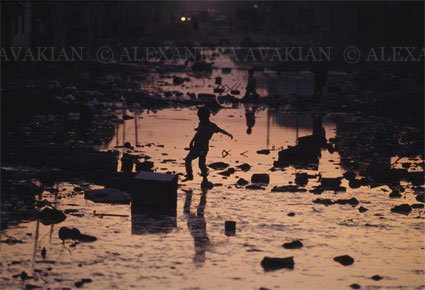 Silhouette of an Iraqi boy crossing a river of sewage