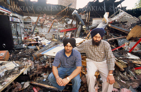 Two Sikh-Americans sitting amongst the remains of their destroyed business