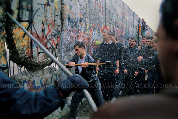 A man swings a sledgehammer at a fractured portion of the Berlin Wall, while onlookers cheer