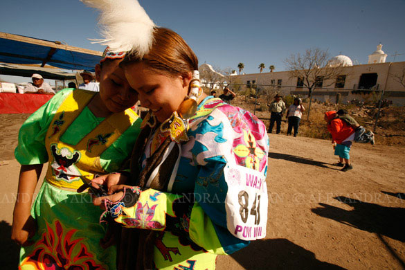 Teenage Native American dancers text messaging between dances during a pow-wow
